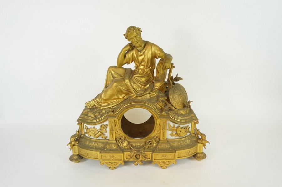 Caisse de pendule en bronze et laiton doré à décor de poète à l'antique et trophées. XIXe siècle. 42 x 42 cm. Diam. : 10 cm (oculus).