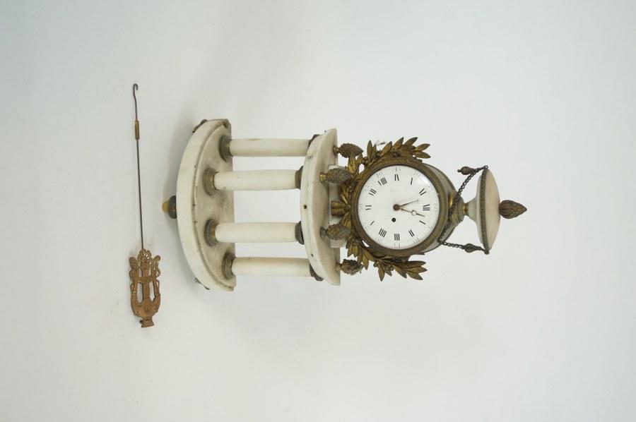 Pendule portique en marbre blanc, décor délicat de feuillages et cassolette. Époque Louis XVI. H. : 34 cm. Un coin du marbre accidenté. Mécanisme en partie manquant, platine marquée LEVASSEUR à PARIS. ON Y JOINT un balancier.