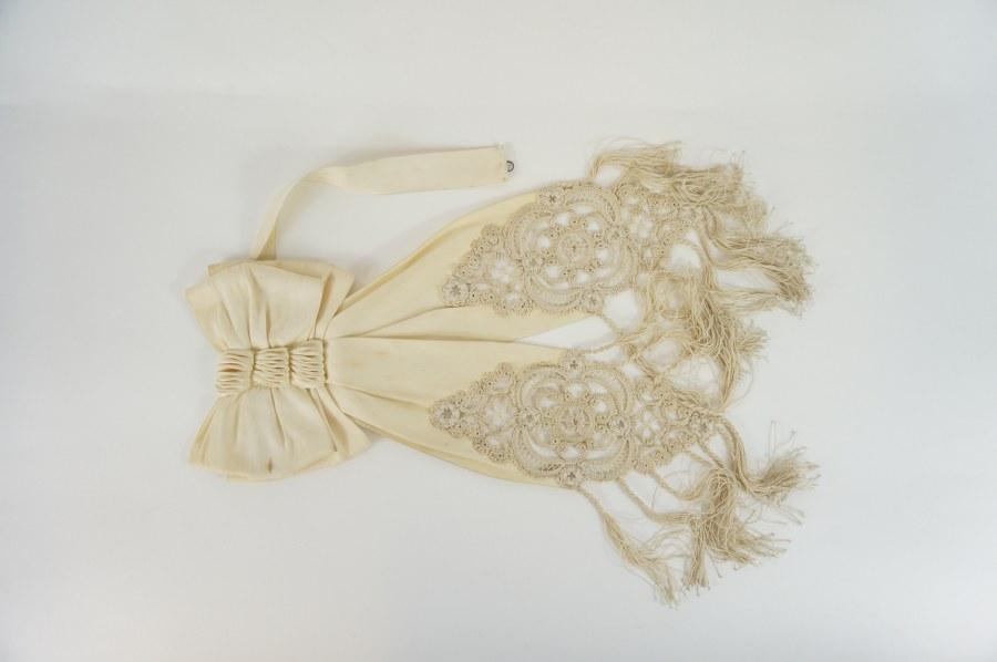 Brassard de confirmation ou de communion en soie blanche plissée en triple nœuds, double volants à décor de dentelles et franges. Fin du XIXe - Début du XXe siècle. Piqûres.