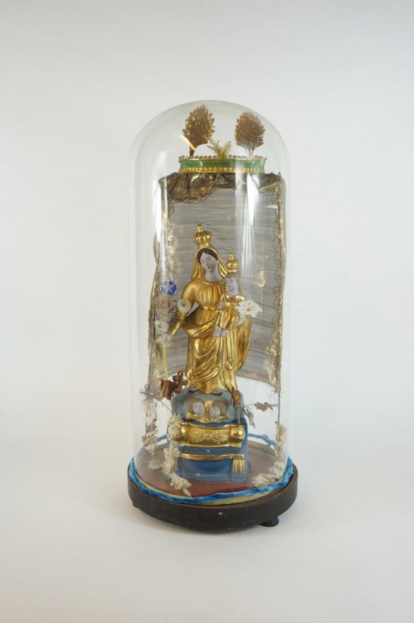 Globe de dévotion représentant la Vierge dite de Marseille et l'Enfant en terre cuite peinte et dorée sous un dais en métal et tissu agrémenté de fleurs en tissus, sous un globe de verre et reposant sur une base en bois noirci. Travail du XIXe siècle. H. : 50 cm.