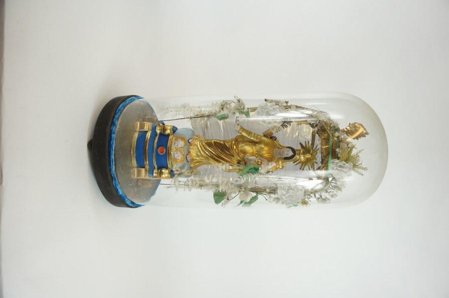 Globe de dévotion représentant la Vierge dite de Marseille et l'Enfant en terre cuite peinte et dorée sous un dais en métal et tissu agrémenté de fleurs en tissus, sous un globe de verre et reposant sur une base en bois noirci. Travail du XIXe siècle. H. : 55 cm. Trous de vers.