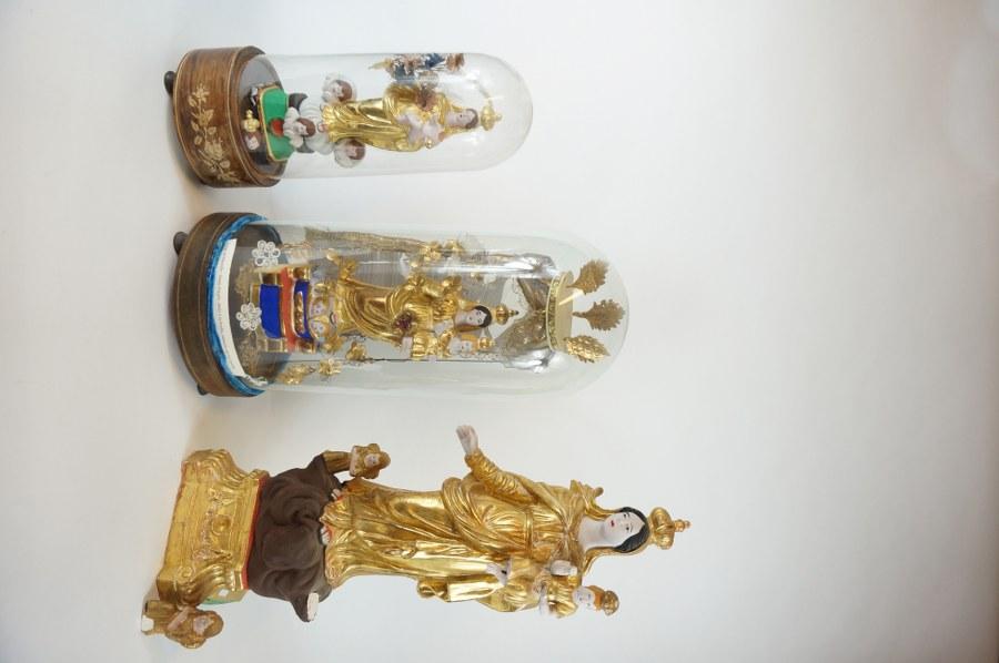 Lot comprenant deux globes de dévotion représentant la Vierge dite de Marseille et l'Enfant en terre cuite peinte et dorée sous un dais en métal et tissu agrémenté de fleurs en tissus, sous un globe de verre et reposant sur une base en bois noirci pour l'une, marqueté pour l'autre. Travail du XIXe siècle. H. : 55 cm. ON Y JOINT Une Vierge de Marseille en terre cuite polychromée et dorée. Accidents.