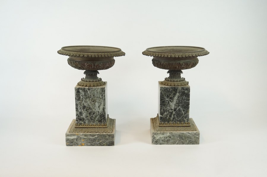 Garniture composée de deux coupes circulaires sur pied en métal ciselé d'un décor d'accantes et rinceaux, reposant sur une base quadrangulaire en marbre vert. Époque Napoléon III. H. : 28 cm.