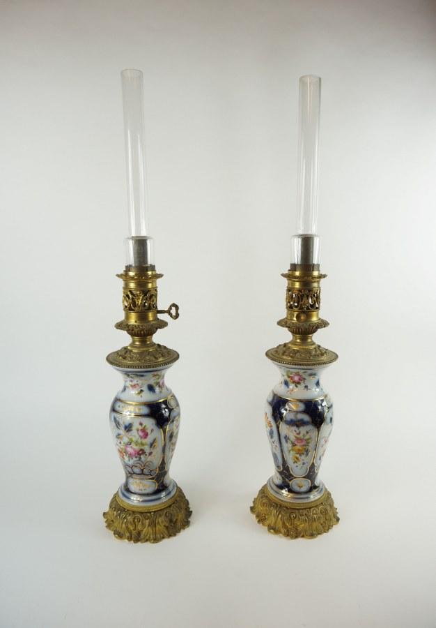 Paire de vases en porcelaine de Bayeux à décor floral en cartouches sur fond bleu montés en lampe à huile. XIXe siècle. H. : 42 cm (lampe) et 72 cm (verre).