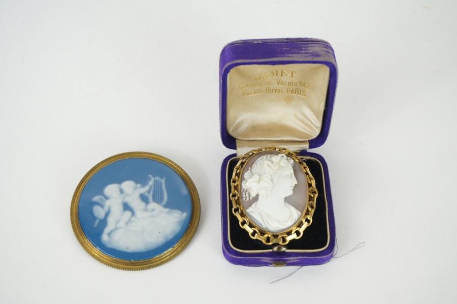Lot de deux broches, un camée sur coquille de la seconde moitié du XIXe siècle et un métal émaillé avec deux angelots dans le goût de WEDGEWOOD.