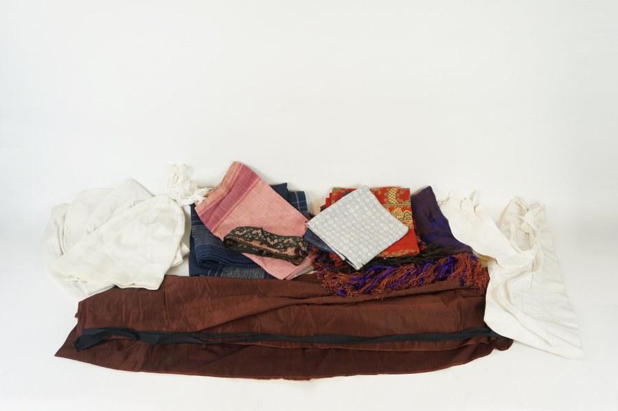 Éléments de costumes traditionnels normands dont châles, tabliers, gants, bonnets, poches… Textiles variés dont coton et soie. XIXe - XXe siècle. Usures, restaurations, salissures.