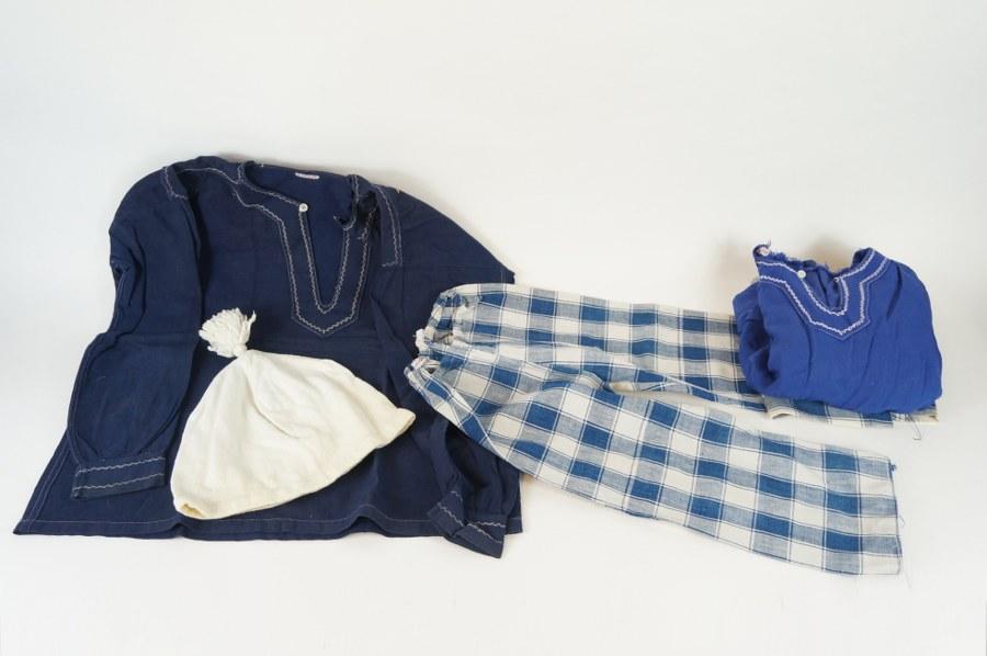 Partie de costumes d'enfant traditionnels normand comprenant deux chemises, deux braies à carreaux et un bonnet à pompon. Coton teinté. XIXe - XXe siècle. Usures éparses.