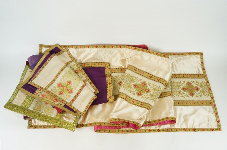 Ensemble textiles de parement d'autel composé de six pans de tissus à riche gallons brodés de rinceaux stylisés et de croix aux fils d'or et fils métalliques sur soie beige, synthétique et moire de soie violette. XIXe - XXe siècle. État d'usage.