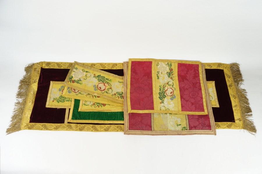 Ensemble textiles de parement d'autel composé de six pans de tissus à riche gallons brodés de rinceaux de roses et volutes argentés aux fils d'or et fils métalliques sur velours cramoisi, velours vert et damas de soie rose. XIXe siècle. État d'usage.