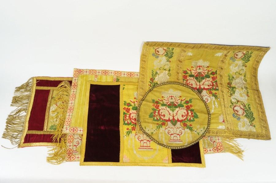 Ensemble textiles de parement d'autel composé de six pans de tissus à riche gallons brodés de rinceaux de roses et volutes argentés aux fils d'or et fils métalliques sur velours cramoisi et velours jaune. XIXe siècle. État d'usage.