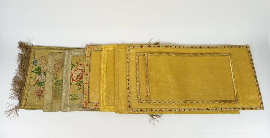 Ensemble textiles de parement d'autel composé de neuf pans de tissus à fond de drap d'or ou gallons brodés de roses et volutes aux fils d'or et fils métalliques. XIXe siècle. État d'usage.