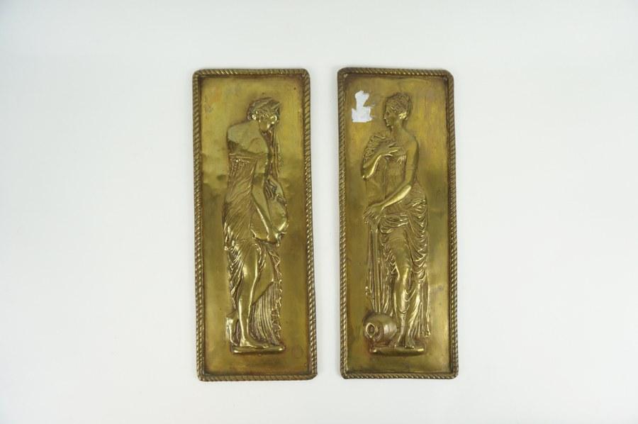 Deux cuivres repoussés représentant des figures allégoriques marines féminines, l'une tenant une cruche, l'autre une rame. 32 x 12 cm.