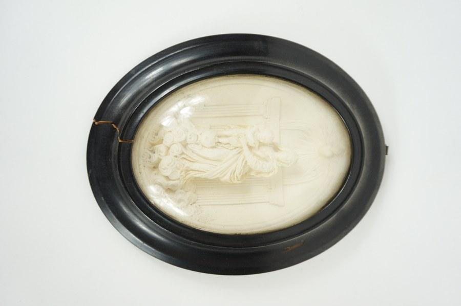 Vierge à l'Enfant. Relief en plâtre sculpté dans un cadre en bois noirci sous verre ovale. XIXe siècle. 25 x 20 cm. Accident au bois.