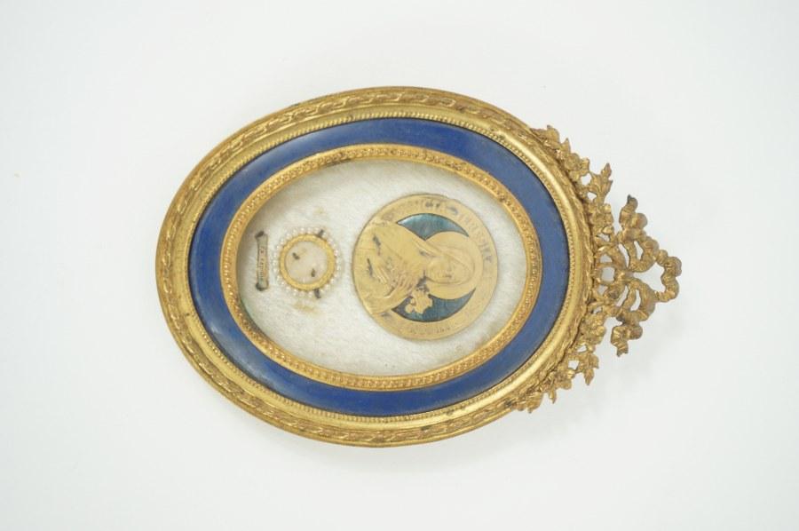 Reliquaire de sainte Thérèse, cadre en métal doré émaillé bleu à décor de rubans, fond de velours blanc. XIXe siècle. 12 x 9 cm.