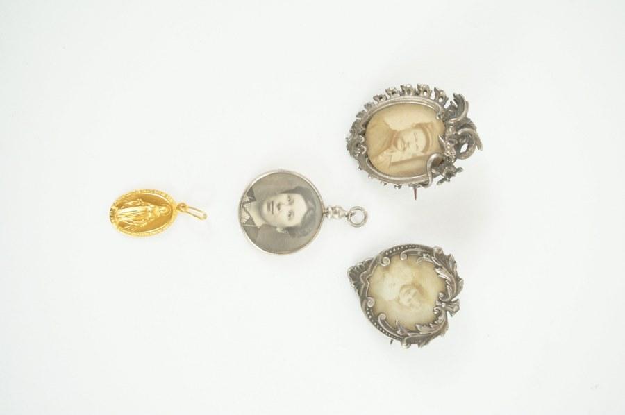 Lot de quatre pendentifs dont trois porte-photographies en argent et métal. Vers 1910-1920.