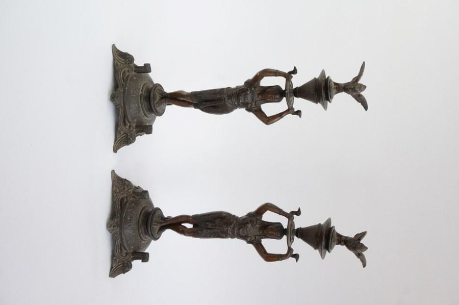 Paire de bougeoirs en régule à décor d'égyptiennes. Fin du XIXe - Début du XXe siècle. Tiges à resserrer, petits accidents.