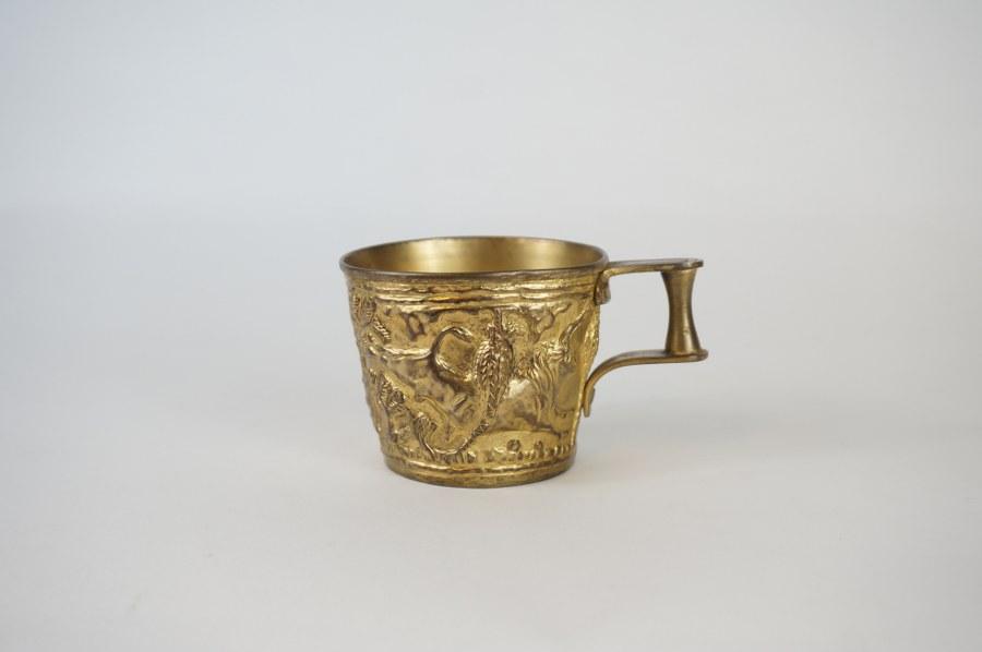 Gobelet à anse représentant des acrobates et des taureaux, reproduction d'une pièce du Minoen. Bronze fondu. Milieu du XXe siècle. H. : 6,5 cm. Diam. : 8 cm.