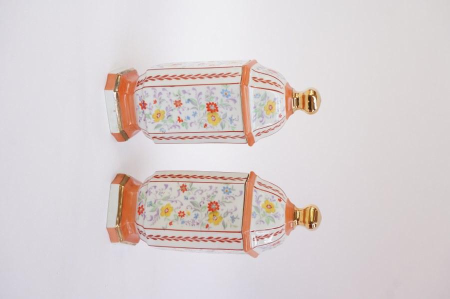 Paire de pots couverts en porcelaine à décor floral. H. : 24 cm.