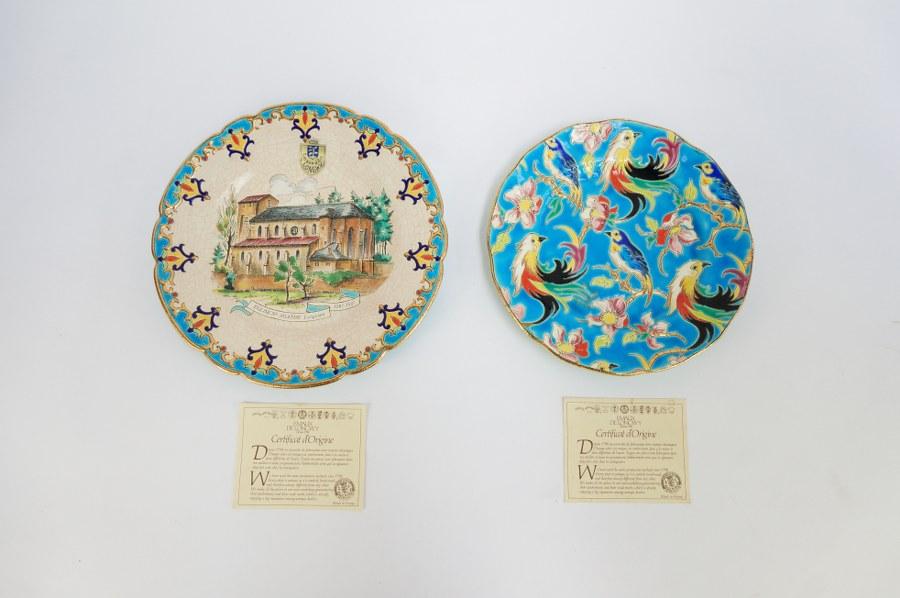 Deux assiettes en faïence glaçurée dite émaux de LONGWY, l'une commémorative de l'église Sainte-Agathe de Longwy, l'autre à décor d'oiseaux de Paradis. Signés sous la base, avec leurs certificats. Années 1980.