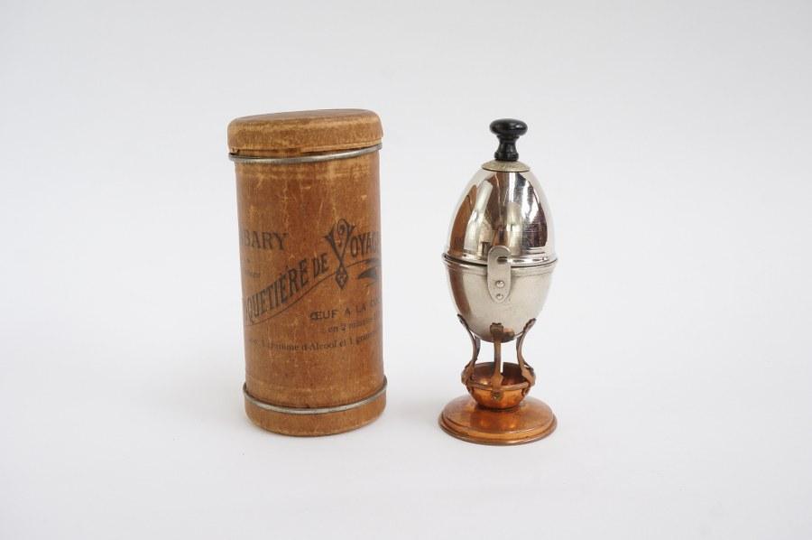 Curieux coquetier La Coquetière par A. BARBARY, appareil de cuisson en métal dans sa boîte en carton bouilli. Début du XXe siècle. H. : 15 cm. Manque le réchaud.