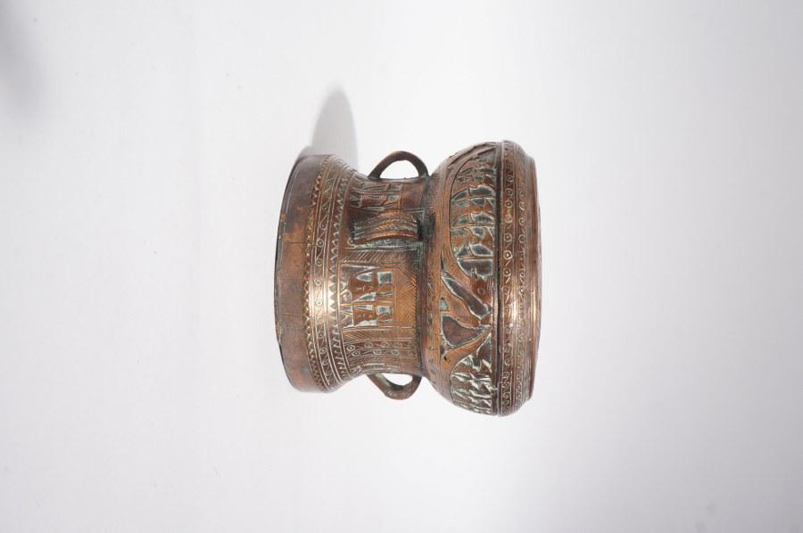 Tambour de pluie vietnamien miniature, retour de voyage, décor en registres gravés de personnages et d'oiseaux. Alliage cuivreux. XXe siècle. H. : 10. Diam. : 12 cm.