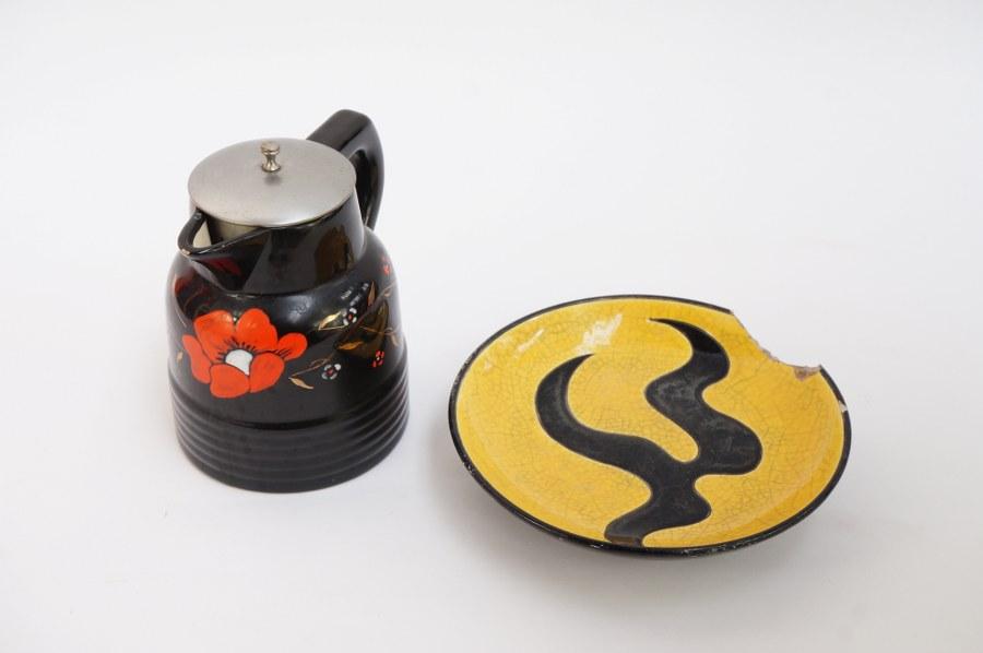 Tisanière et plat en faïence glaçurée dite émaux de LONGWY à fond noir, décor n°3377 pour la tisanière. Plat très accidenté.