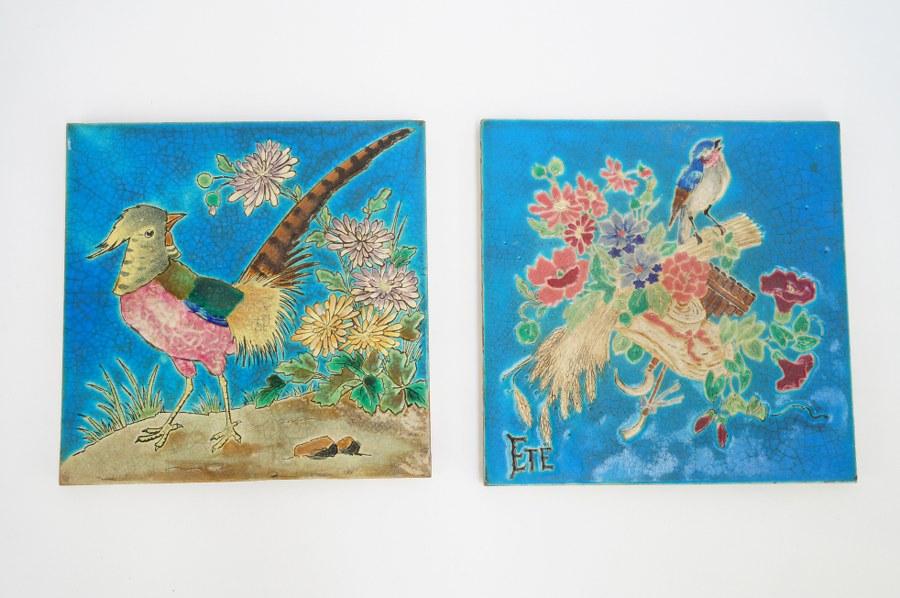 Paire de carreaux en faïence glaçurée dite émaux de LONGWY à décor d'oiseaux et fleurs sur fond bleu, l'un marqué Été. Les deux estampés LONGWY FRANCE au dos. Environ 21 x 21 cm.