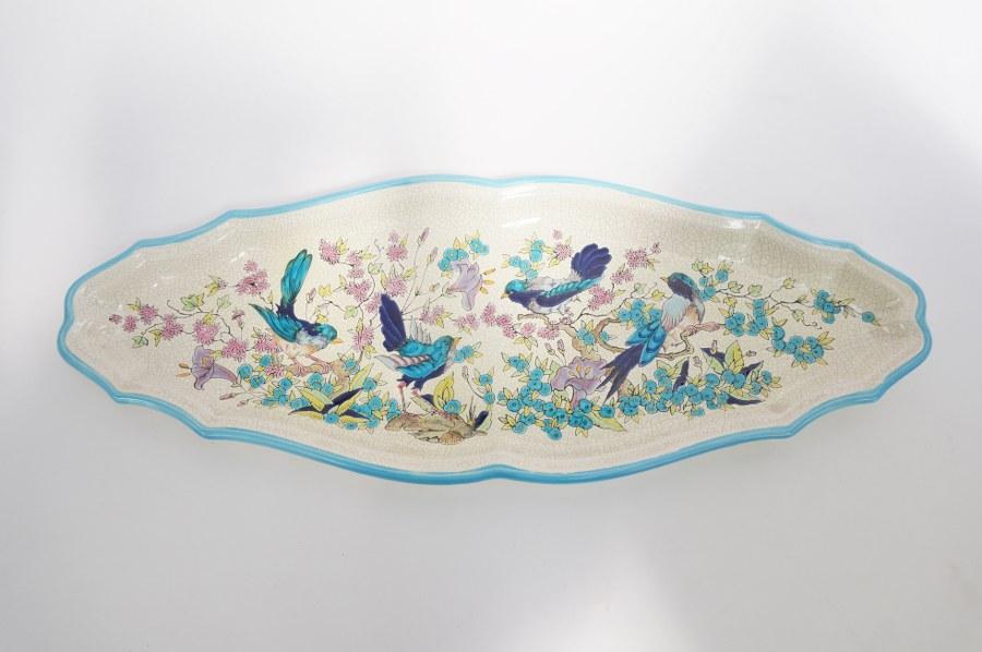 Grand plat à poisson à décor d'oiseaux et de rinceaux fleuris en faïence glaçurée dite émaux de LONGWY à décor Vieux Longwy. Signé sous la base MANUFACTURE LORRAINE SAINT-JEAN L'AIGLE. 63 x 23 cm.