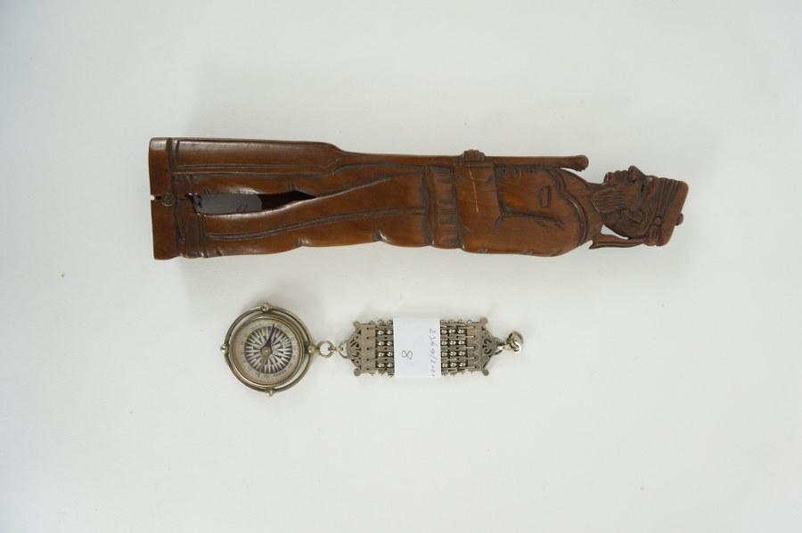Lot comprenant un étui à plumes à couvercle sculpté d'un marin en bois et une boussole à décor d'ancre. XIXe siècle.