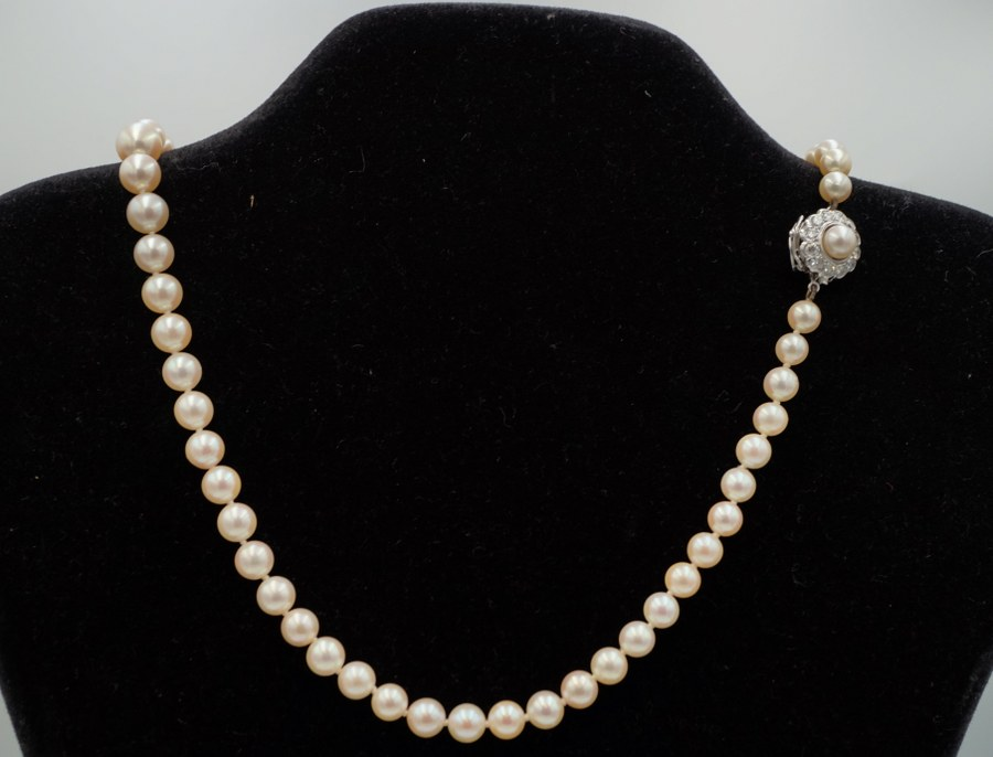 Collier de perles de culture, le fermoir en or blanc (750°°°) à décor de fleur serti d'une perle centrale dans un entourage de brillants.
