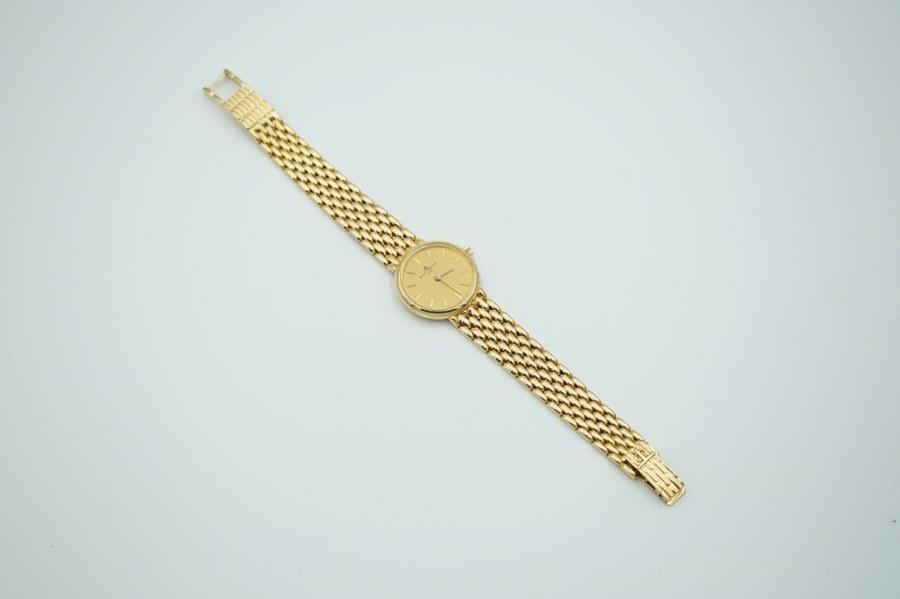 Baume & Mercier. Montre de dame en or jaune (750°°°), le bracelet à mailles articulées. Poids brut : 37, 5 gr.