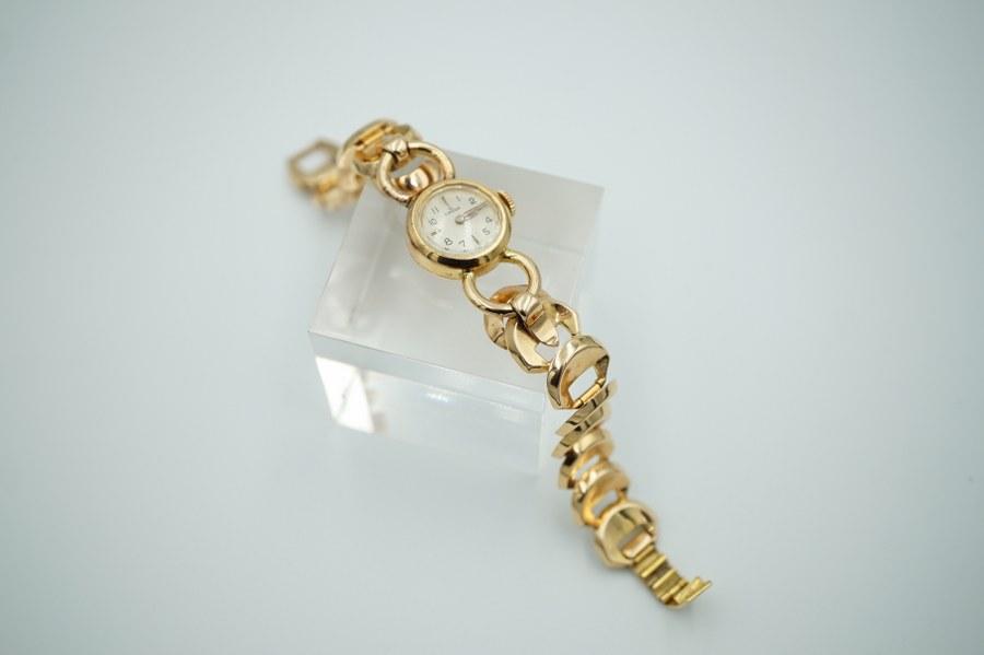 Omega. Montre de dame en or jaune, le cadran émaillé figurant les heures en chiffres arabes, les bracelet à mailles articulées. Poids brut : 35, 1 gr.