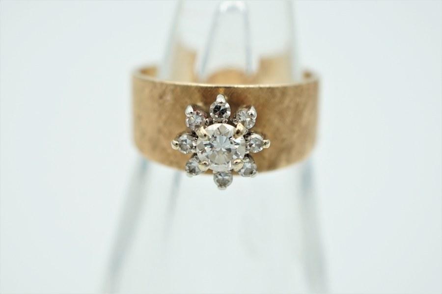 Bague en or jaune brossé (750°°°) sertie d'un diamant central dans un entourage de brillants. TDD : 52. Poids brut : 4gr.