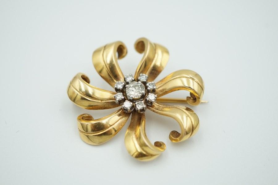 Broche fleur en or jaune (750°°°), sertie en son centre d'un diamant central dans un entourage de brillants. Poids brut : 8, 2 gr.