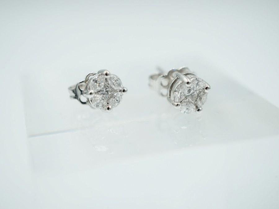 Paire de boutons d'oreilles ronds en or blanc (750/°°°).  Ornés en leur centre de deux diamants taille princesse entourés de huit diamants taille navette. Poids brut : 2,05 gr.