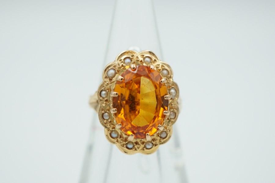 Bague en or jaune (750°°°), sertie d'une citrine de forme ovale dans un entourage de perles. TDD : 51. Poids brut : 6, 4 gr.