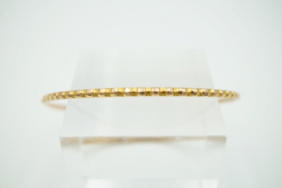 Bracelet anneau en or jaune iranien à décor de dentelure. Poids : 6,8 gr.