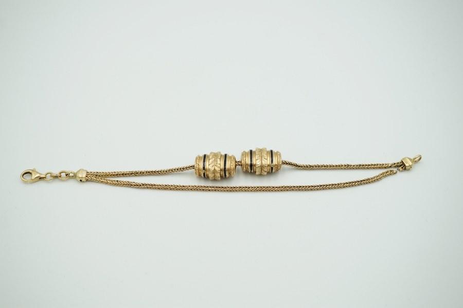 Chaîne de montre et breloques en or jaune (750°°°) partiellement émaillée. Poids brut : 11,3 gr.