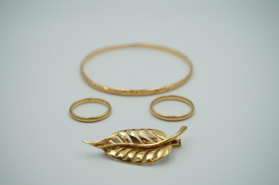 Lot de bijoux en or jaune (750°°°) comprenant un bracelet rigide, deux alliances, une briche à décor de feuille et une bague à décor de rinceaux. Poids : 27 gr.