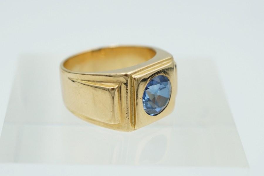Chevalière en or jaune (750°°°) sertie d'une pierre facettée bleue. TDD : 50/ Poids brut : 12 gr.