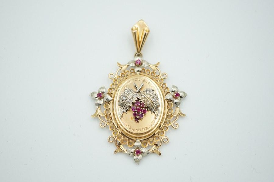 Pendentif porte-photographie en or jaune (750°°°).  A décor de feuille de vigne, serti de pierres de couleur. Poids brut : 15, 5 gr.