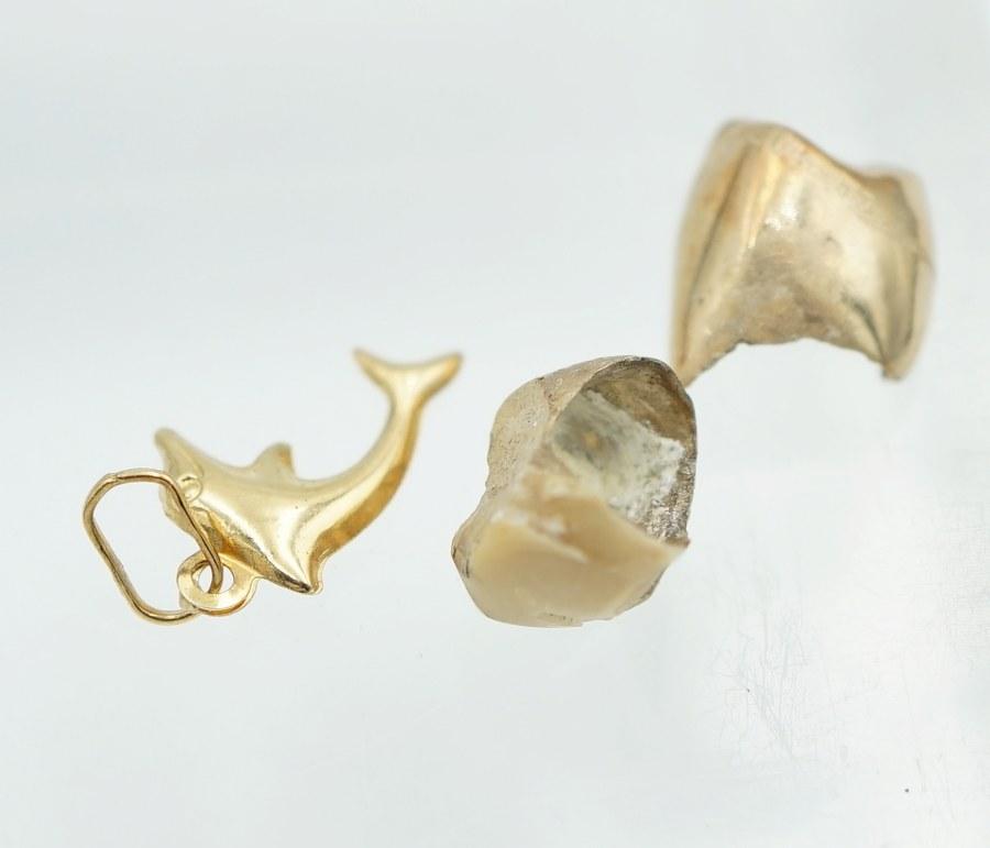 Or dentaire et pendentif en forme de dauphin. Poids brut : 2, 6 gr.