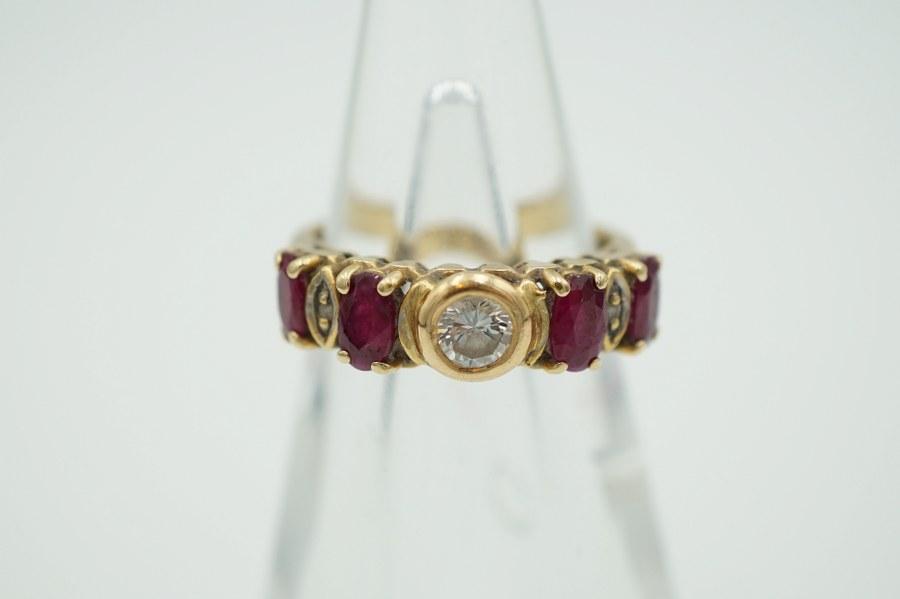 Bague en or jaune (750°°°) sertie de quatre rubis et d'un brillant d'environ 0,25 crts.