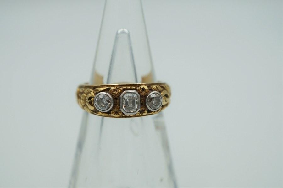 Bague en or jaune (750°°°) gravé de fleurettes, sertie de trois diamants sertis clos. TDD : 58. Poids brut : 11, 2 gr.