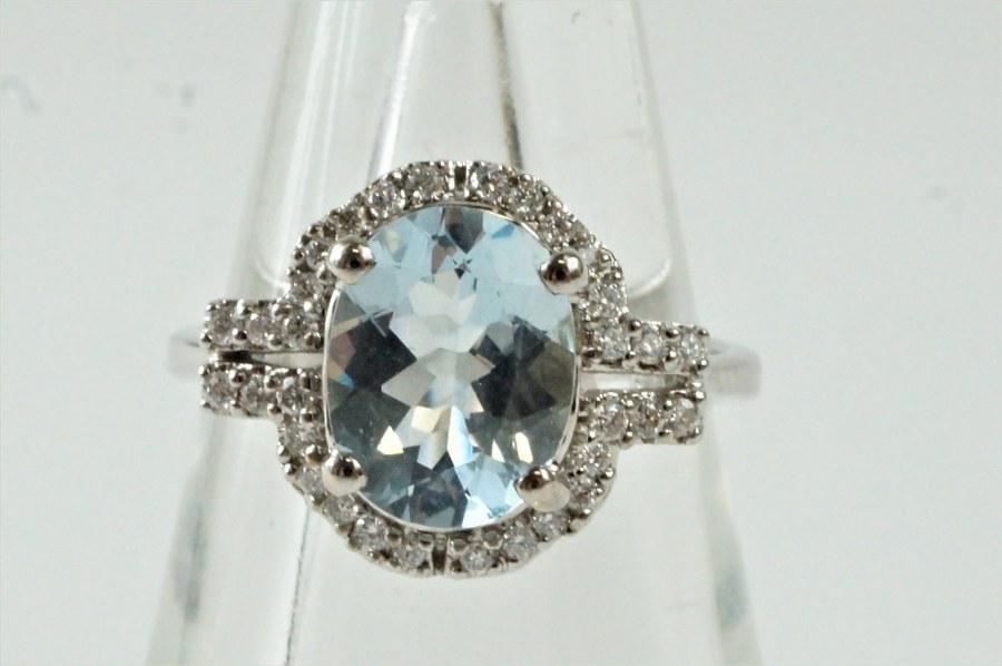 Bague en or blanc (750°°°)  sertie d'une aigue marine. De taille ovale de 1,65 carat, dans un entourage de 32 diamants blancs taille moderne.    Poids brut : 3,90 gr. TDD : 54.