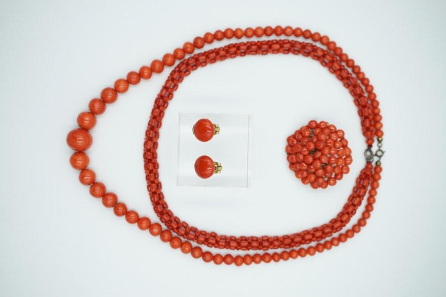 Parure en corail comprenant deux colliers, une broche circulaire et une paire de boucles d'oreilles à clip.