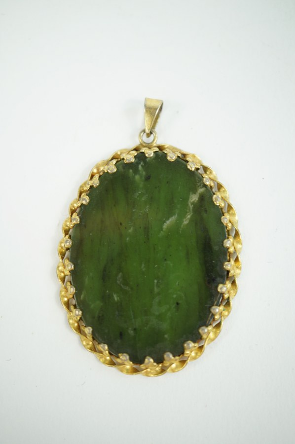 Pendentif de forme ovale en métal doré  et pierre dure verte. Hauteur : 4.5 cm.