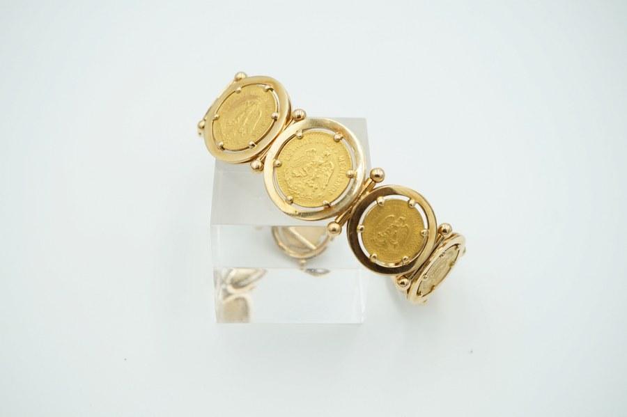 Bracelet en or jaune (750°°°) à mailles articulées circulaires serties de quatre pièces de 1/2 Pesos et deux pièces de cinq Pesos. Poids : 58 gr.