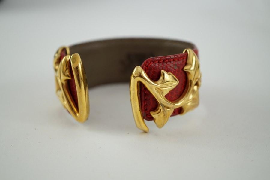 Bracelet de cuir rouge et ornementation en métal doré de marque VAN DER BAUWEDE. ON Y JOINT Une montre mécanique portant la marque ROLEX OYSTER PERPETUAL en acier doré. Manque une des couronnes.