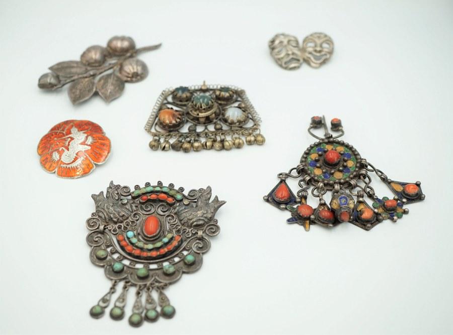 Lot de bijoux et biens en argent dont broches, bijoux marocains et berbères, sertissages de pierres, corail, verre, certaines émaillées. Poids brut : 133 gr.